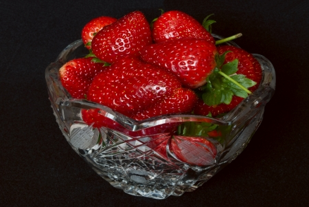 Crystal vase with red strawberries on a black background  Stock Photo