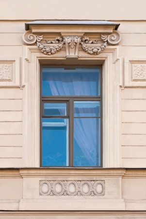 A window with bas-relief on the background of beige wall  From the series window of Saint-Petersburg