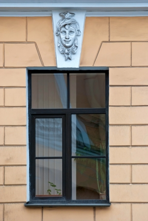 A window with bas-relief on the background of beige wall  From the series window of Saint-Petersburg  photo