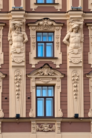front elevation: The facade of the building with Windows and antique sculptures  Stock Photo