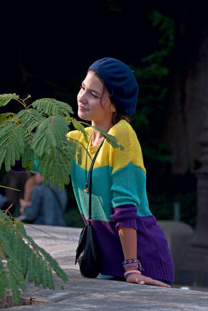 Girl in the blue beret,  is watching with interest the leaves of a fern  photo