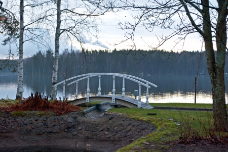 White bridge on a background of lake and forest in a park on the shore of the lake near the town of Heinola in Finland  photo