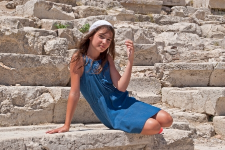 Girl, sitting on a stone bench rostrum of the ancient theatre on the territory of the Acropolis of Athens in Greece
