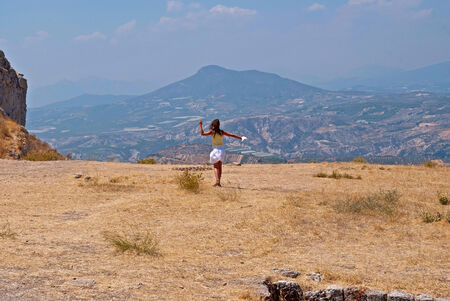 Girl on a plateau of ancient Corinth, on the background of mountains  Stock Photo