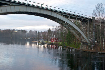 Railway bridge on the evening park views on the lake near the town of Heinola in Finland