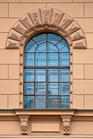 Window with arch and a bas-relief of beige wall  From the series window of Saint-Petersburg  photo