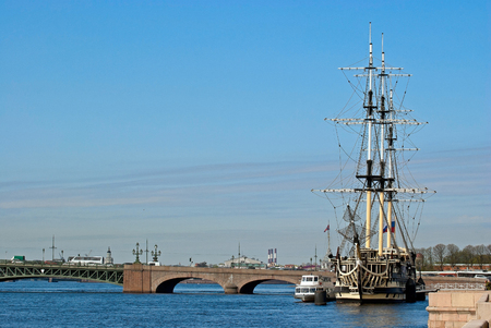 View of the bridge across the Neva River and the old sailing ship in a sunny summer day in the city of Saint-Petersburg  photo
