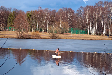 Fisherman catches a fish in a pond Primorsky Victory Park in Saint-Petersburg