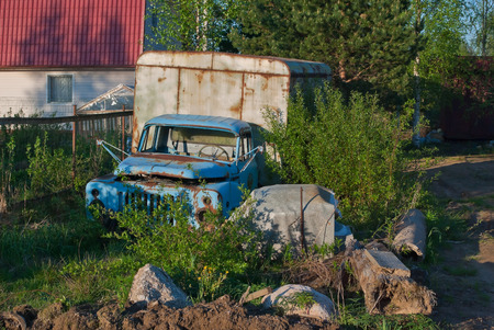 Old derelict truck on a country site overgrown with bushes  photo