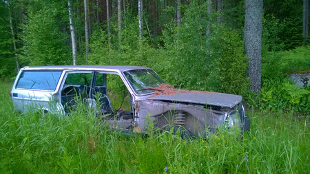 Old derelict car lost in the woods