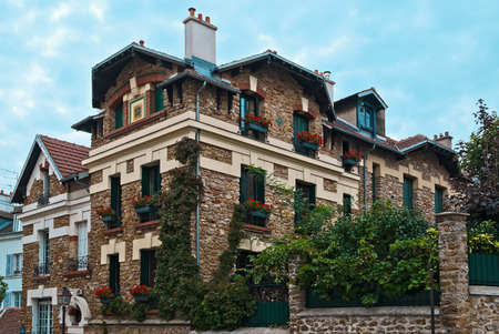 Beautiful house in the Victorian style of beige brick with flowers and greenery in Paris in Montmartre in the summer on a sunny day.