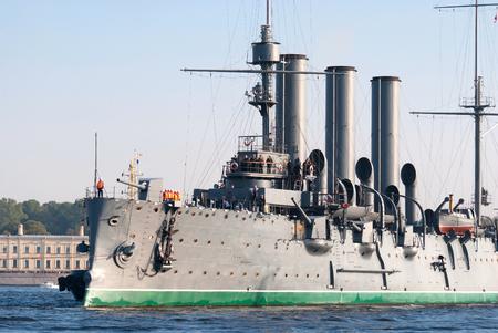 Towing cruiser Aurora on the river Neva major overhaul the docks of the island of Kronstadt. Stock Photo