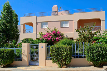 Pink house with a fence and flowering trees on a street in the city Saronida in Greece.