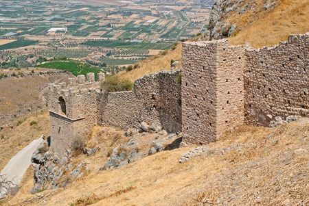 The walls of the old fortress of the ancient city of Corinth on the mountainside on a sunny day. Peloponnese, Greece.