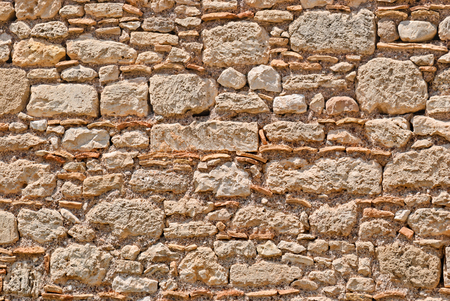 Part of the fortress wall of light beige stone in the ancient city of Corinth. Peloponnese, Greece. Stock Photo