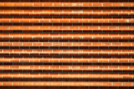 Part of the wall of the house of tan brick red with a shadow from the grid.