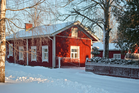 Wooden house with red walls and white Windows frosty winter morning in the Finnish town of Forssa.