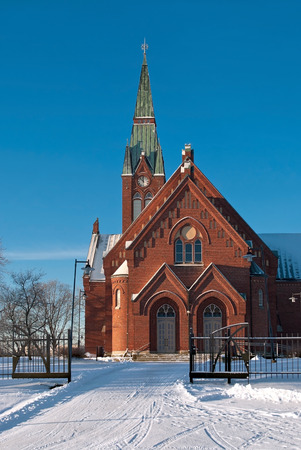 The Evangelical Lutheran Church of red brick on the background of blue sky in the Finnish town of Forssa.