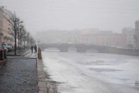 Fog on the embankment of the Neva River in the early morning in February in the city of Saint Petersburg.