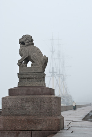 Granite sculpture Chi-Tsang on the embankment of the river Neva on the background of an old sailing ship early on a misty morning in the city of Saint Petersburg. Stock Photo