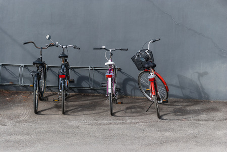 Four bicycles parked near the gray wall in the sandy track.