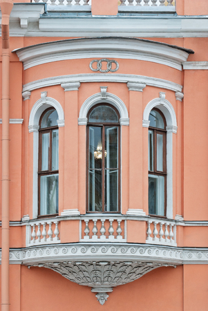 The pink facade of the building with Windows on the alcove and basrelief. From the series window of SaintPetersburg. Stock Photo
