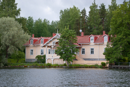 Beige house with a roof of red tiles on the lake, in the evening, near the town of Heinola in Finland. Stockfoto
