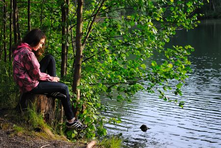 A girl sitting on the bank of forest lake on a summer evening.