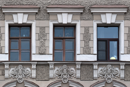 Facade of grey building with three rectangular Windows and a bas-relief. From the series window of Saint-Petersburg.