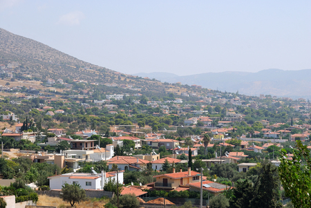 Greek village Anavisos, spread out on the mountainside on a bright sunny day. Greece.