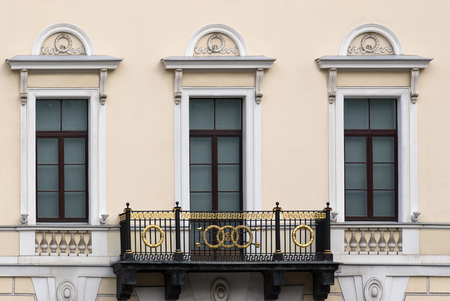 balcony window: Facade beige building with three rectangular windows and a balcony. From the series window of Saint-Petersburg.