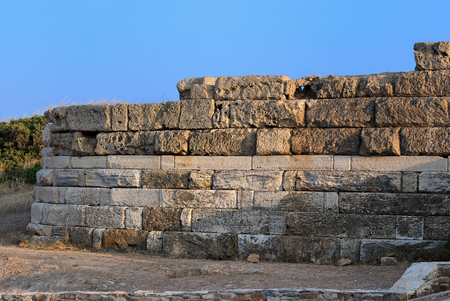 A fragment of the old walls of the ancient Temple of Poseidon at Cape Sounion in the warm summer evening. Greece.
