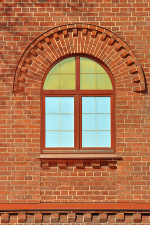 Window with an arch on the background wall of red brick. From the series window of Saint-Petersburg. Stock Photo