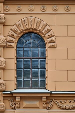 Window with arch and a bas-relief on a background of beige wall. From the series window of Saint-Petersburg. Stock Photo