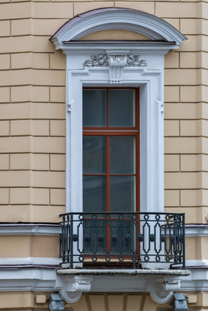 balcony window: A window with an arch and balcony on the facade of the beige building. From the series window of Saint-Petersburg.