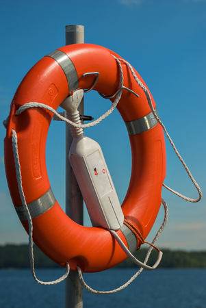 Red lifebuoy on the pier on the background of blue sky and lake.