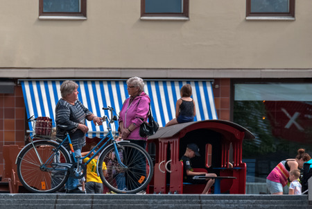 leisurely: IMATRA, FINLAND, June 24: A leisurely conversation between two elderly women on the main street of the Finnish town of Imatra, 24 June 2016.