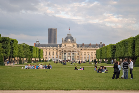PARIS, FRANCE, June 18: Parisians and guests of the city rest on the lawn of the Champs de Mars on 18 June 2012. In the background is the building of the Paris Military school. Editorial