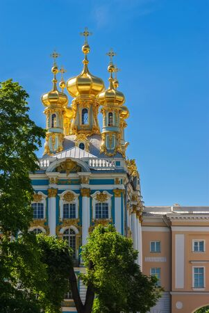 Fragment of the Catherine Palace in Peterhof with gilded domes against the blue sky.
