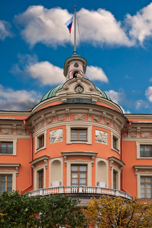 Fragment of the Mikhailovsky castle in Saint-Petersburg with a tower, spire and the Russian flag on blue sky background.