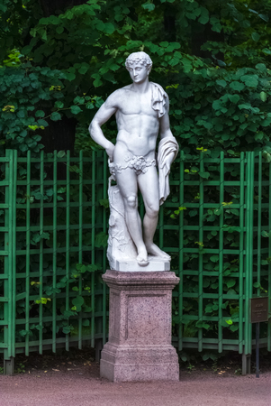 Marble statue on a granite pedestal in the Summer garden on a green background lattice.