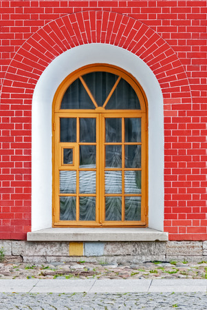 Window with arch in the background of wall of red brick. From the series window of Saint-Petersburg. Stock Photo