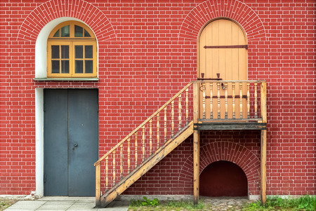 Door, window with arch and stairs and against the wall of red brick. From the series window of Saint-Petersburg.
