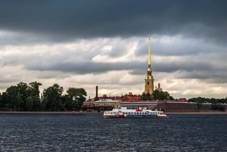 Motor ship, sailing on the river Neva on a background of the fortress in a gray cloudy day in Saint-Petersburg. Stock Photo