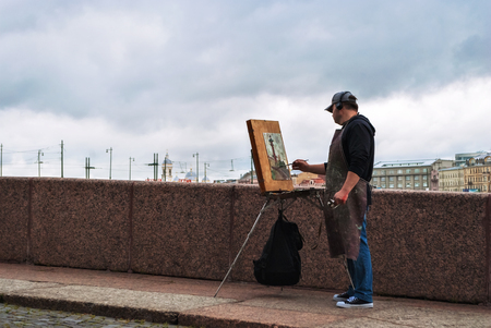 SAINT PETERSBURG, RUSSIA, may 14: the Artist with his easel draws the Rostral column on the spit of Vasilievsky island, 14 may 2016 in Saint-Petersburg.