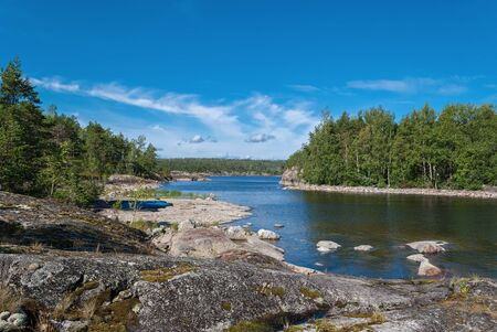 Blue tourist kayaks on the rocky shore of Lake Ladoga on the background of blue sky with white clouds in Karelia.