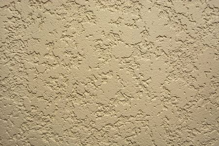Abstract beige background of the spots of brown and white paint on the yellow plastered wall. Stock Photo