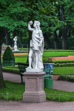 Marble sculpture on a granite pedestal in the Summer garden on a green background lattice. Editorial