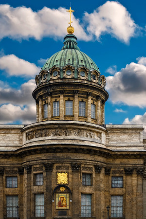 Fragment of the building of the Kazan Cathedral in Saint-Petersburg, with a green dome and gold cross against the blue sky with white clouds.