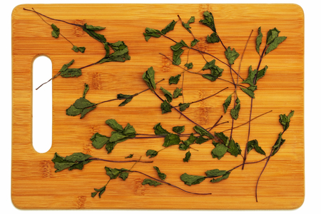 The dried herb mint lying on a cutting board made of bamboo on a white background. Stock Photo